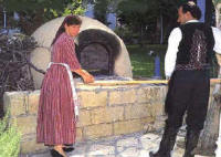 Original bread baking oven tended by a Cypriot couple wearing Cyprus national dress